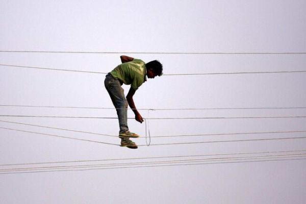 image کارگر اداره برق هند در حال تعمیر کابلهای برق شهر الله آباد