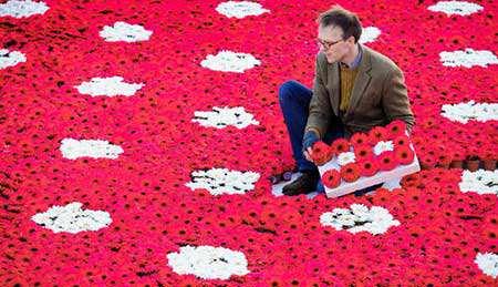 image هنرمند بریتانیایی در حال چینش اثر هنری با گل