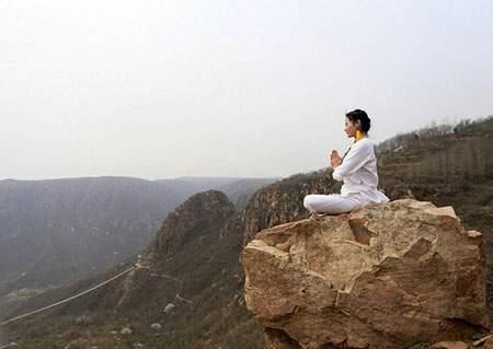 image تصویر آرامش بخش تمرین یوگا زنی بر روی صخره ها چین