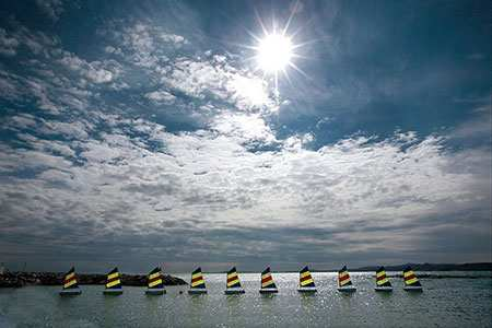 image عکسی از قایق های زیبای بادبانی رنگارنگ در دریایی آرام