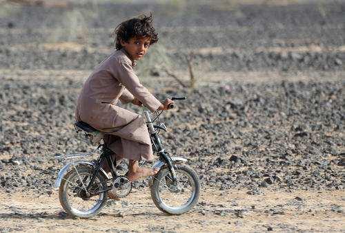 image عکس دوچرخه سواری کودک پابرهنه یمنی شهر مارب